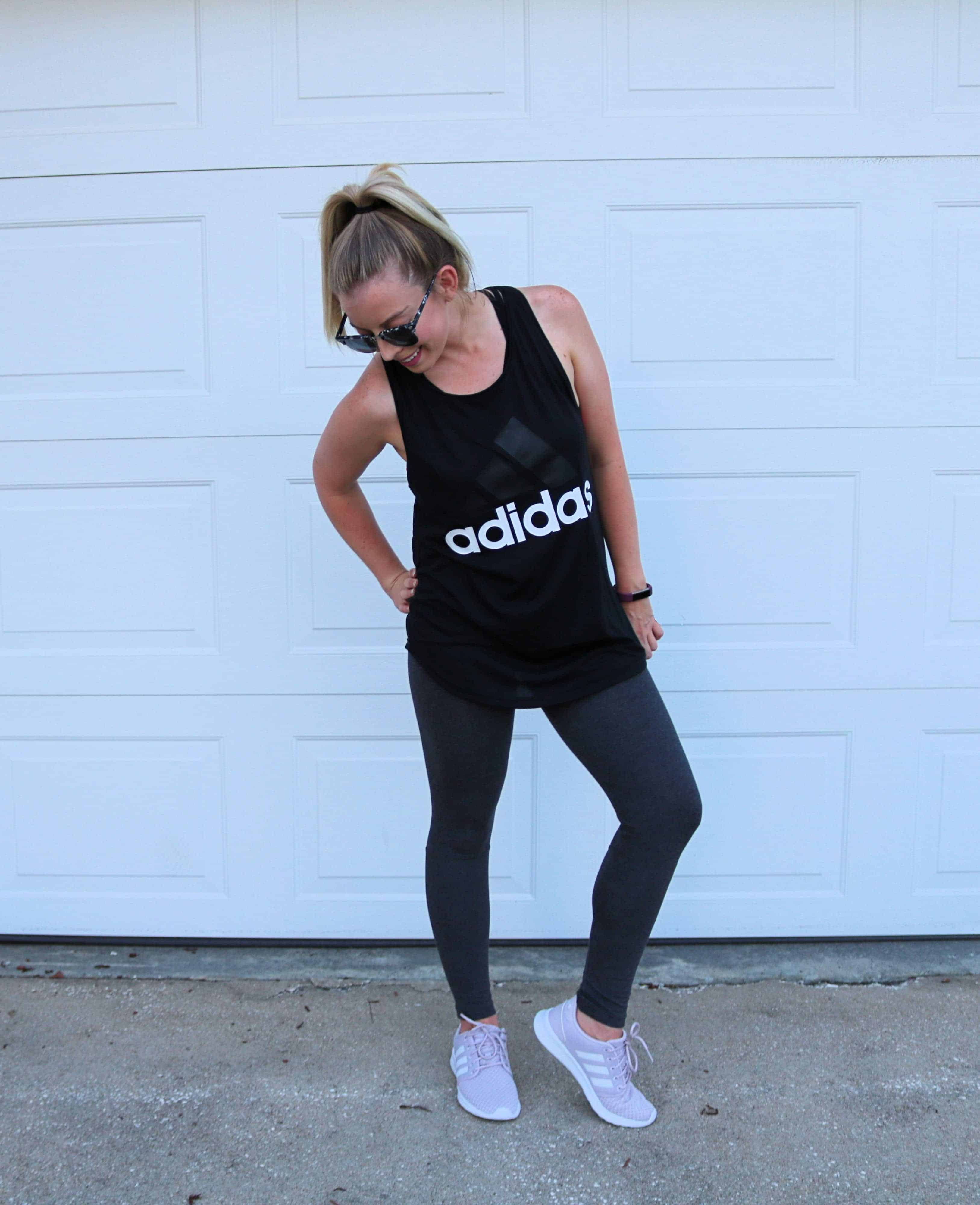 This cute and casual workout outfit from adidas is perfect for wearing in the hot summer months for a good workout or run! I just love the black and white loose tank, high waisted gray and pink leggings, and my super comfy light purple adidas running sneakers! #workoutoutfit #workoutclothes #runningshoes #adidas