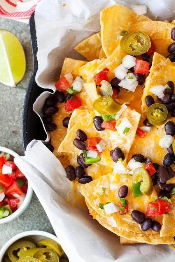 Delicious Skillet Nachos | Need game day recipes for your Super Bowl party? Check out 65 of the best Super Bowl recipes that will feed a crowd including easy and delicious super bowl appetizers, wings, dips, sliders, snacks, desserts, and more! #superbowl #partyfood #superbowlfood #gamedayrecipes #appetizers #snacks