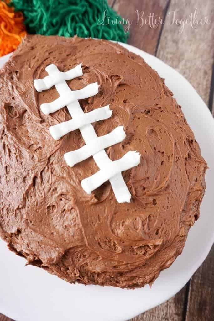 Easy Football Cake | Need game day recipes for your Super Bowl party? Check out 65 of the best Super Bowl recipes that will feed a crowd including easy and delicious super bowl appetizers, wings, dips, sliders, snacks, desserts, and more! #superbowl #partyfood #superbowlfood #gamedayrecipes #appetizers #snacks