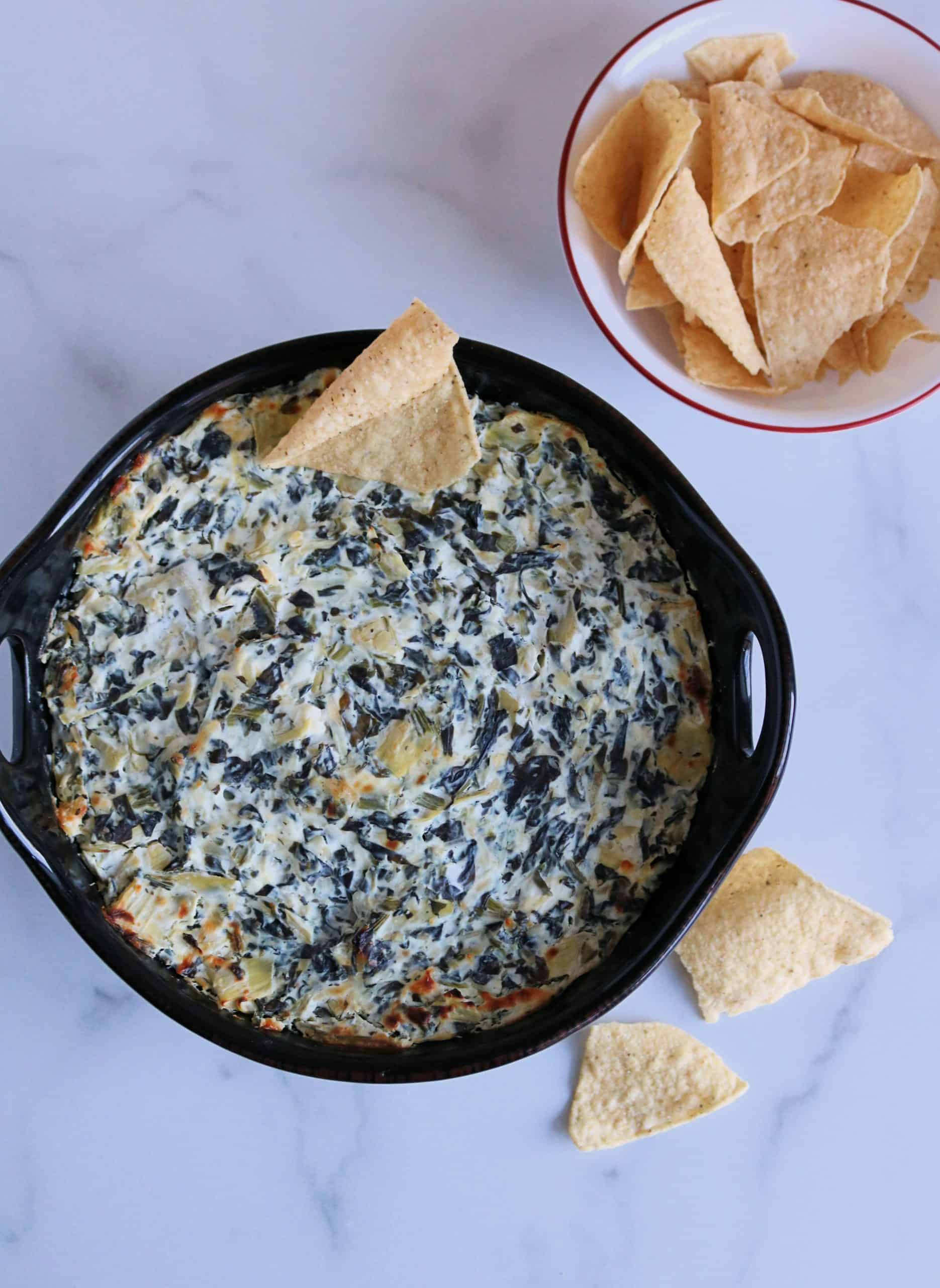 This easy Skinny Spinach Artichoke Dip is low calorie and will quickly become your new favorite party dip or game day appetizer! It's lightened up with cream cheese and Greek yogurt and loaded with healthy spinach, artichokes, three cheeses, and the delicious flavors of garlic and lemon. #spinachartichokedip #appetizer #dip #healthydip #cheesedip #superbowlrecipe