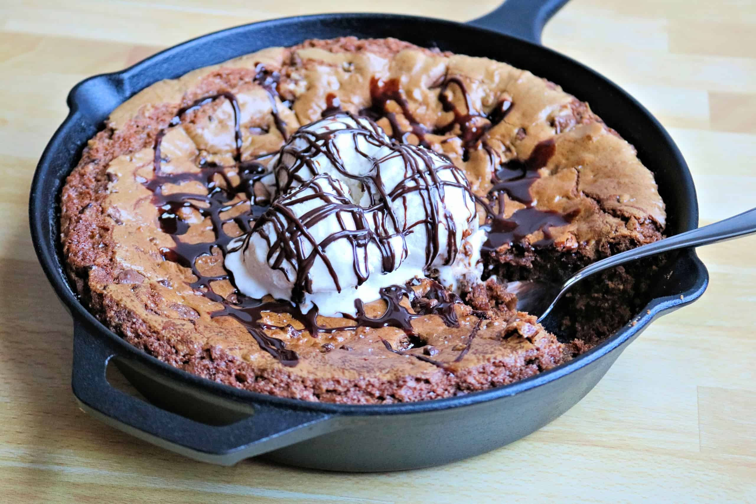 Delicious Brown Butter Chocolate Chip Cookie Skillet Recipe - This easy cast iron cookie skillet features a delicious brown butter cookie dough loaded with mini semi-sweet chocolate chips and milk chocolate chips, and topped with a pinch of sea salt, vanilla bean ice cream, and a drizzle of chocolate sauce for an epic pizookie you can't resist! #skilletcookie #chocolatechipcookie #brownbuttercookie #desserts #pizookie #castiron