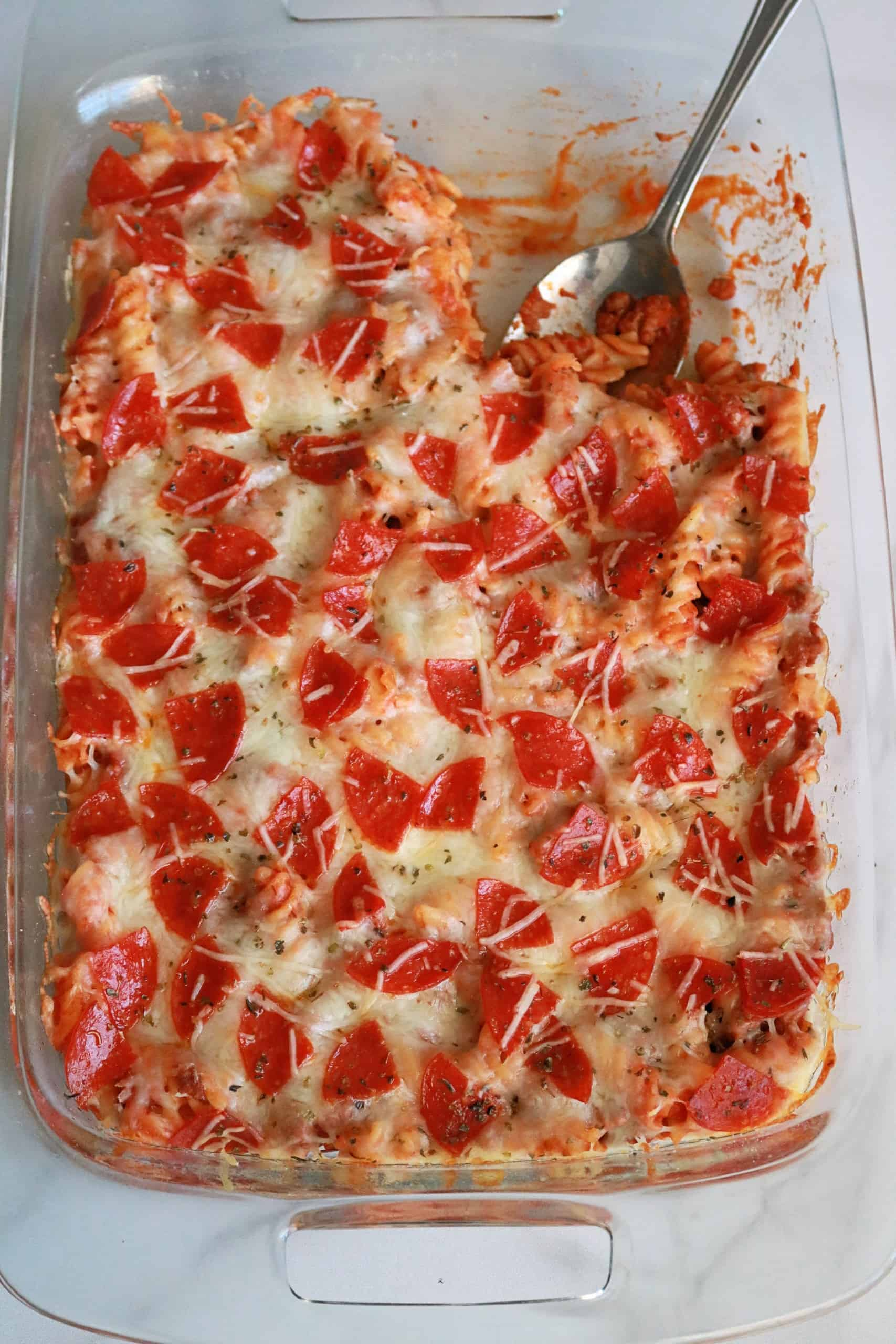 Try my delicious pepperoni pizza pasta bake for an easy weeknight dinner for the family! This pizza casserole is made with pepperoni, sausage, pasta, marinara sauce, herbs, and gooey cheese, and takes less than 30 minutes to make. It's also freezer-friendly! #pizzacasserole #casserole #easydinnerrecipe #pizzapasta