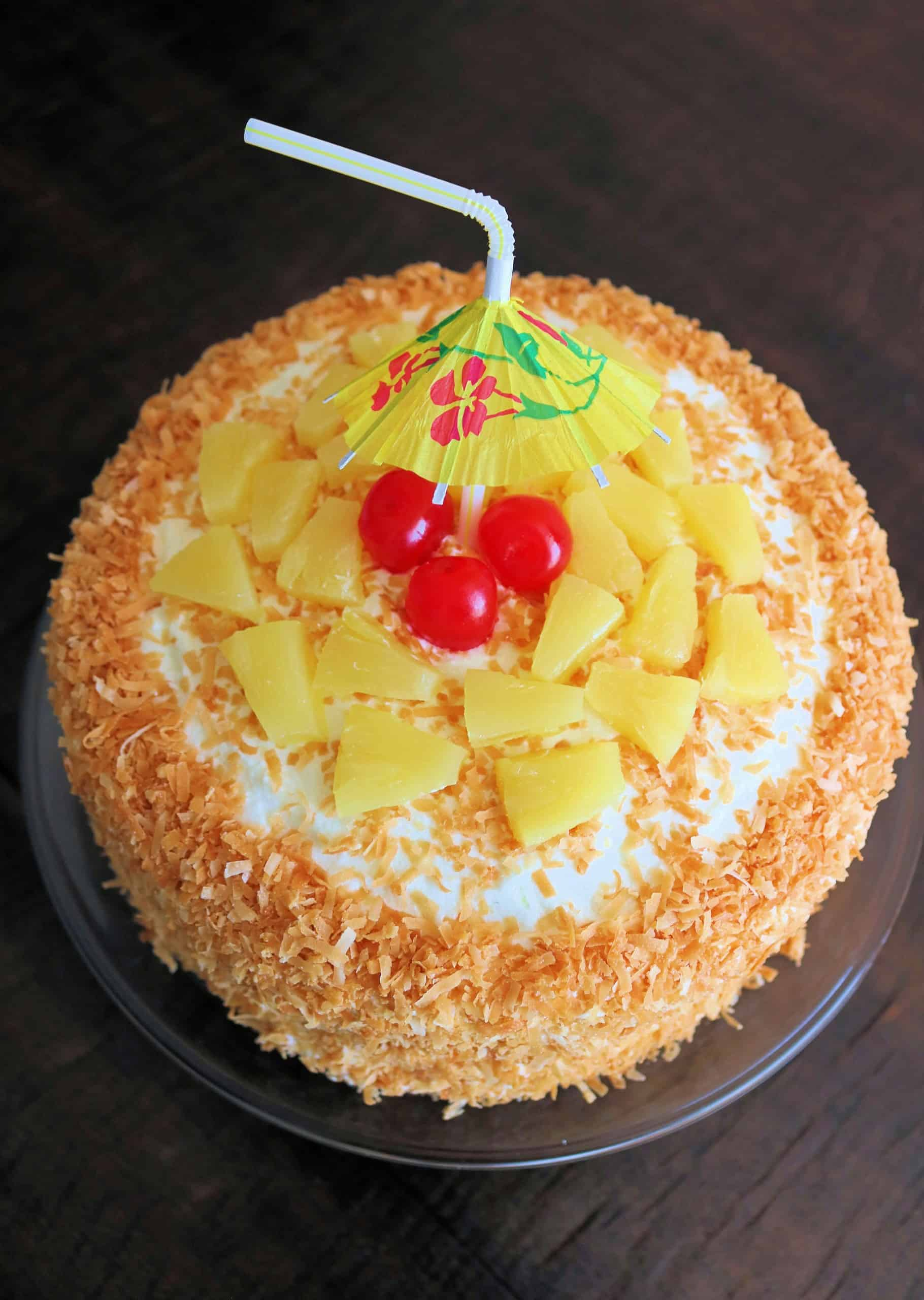 Try my Best Ever Pina Colada Cake with layers of moist pineapple, coconut, and rum flavored cake, a sweet crushed pineapple filling, and a luscious whipped cream cheese frosting coated in toasted coconut. Top it with pineapple, maraschino cherries, and a cute little umbrella, and this incredible pina colada cake will take you on a tropical getaway! #pinacolada #cake #pinacoladacake #coconutcake #pineapplecake #coconutpineapplecake #tropicalcake