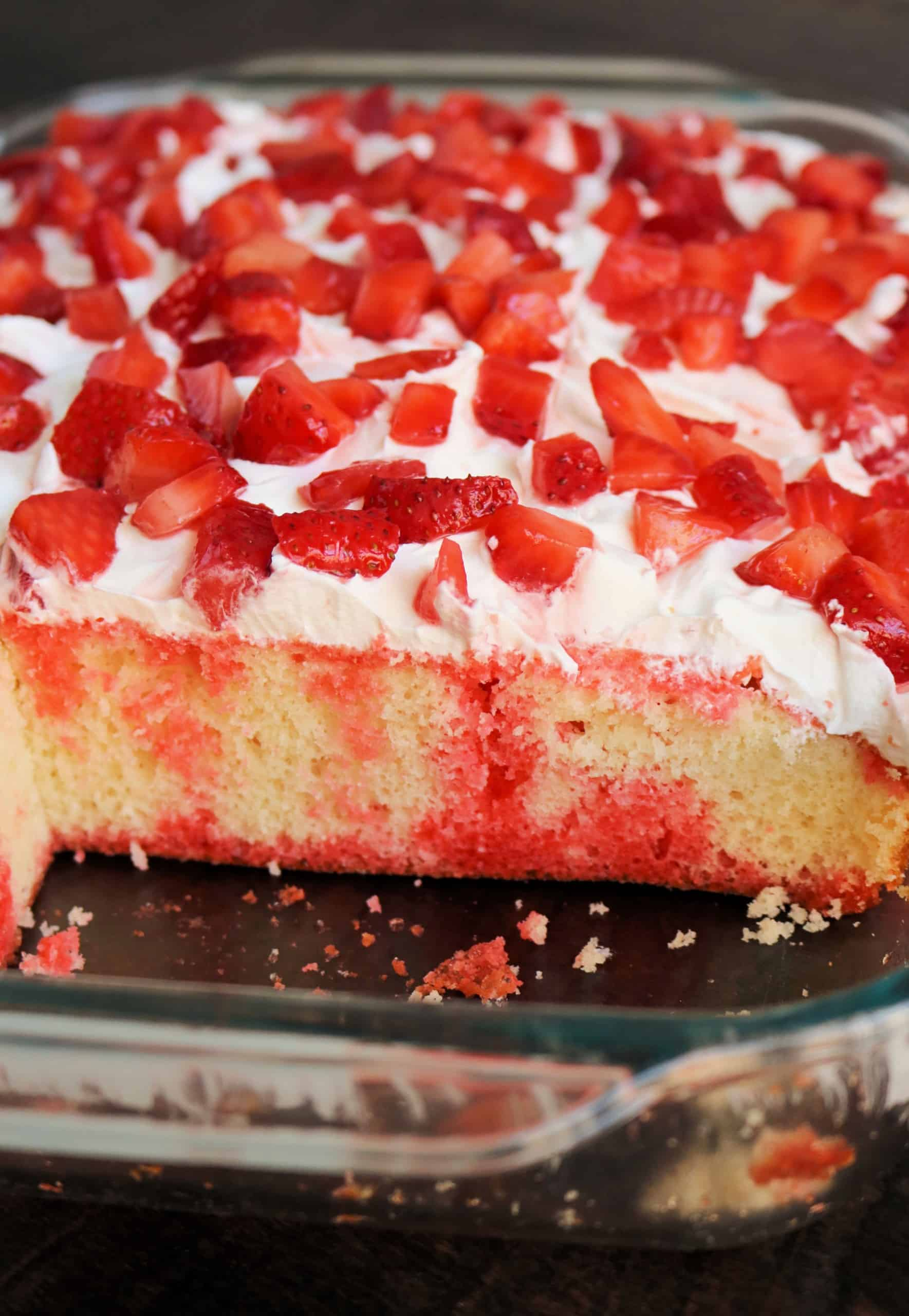 Try my Easy Strawberry Jello Poke Cake for a light and refreshing summer cake your family and friends will love! It's made with just 5 ingredients including fresh strawberries, strawberry jello mix, and whipped cream topping, and is so delicious! #strawberrypokecake #jellopokecake #pokecake #strawberriesandcream #dessert