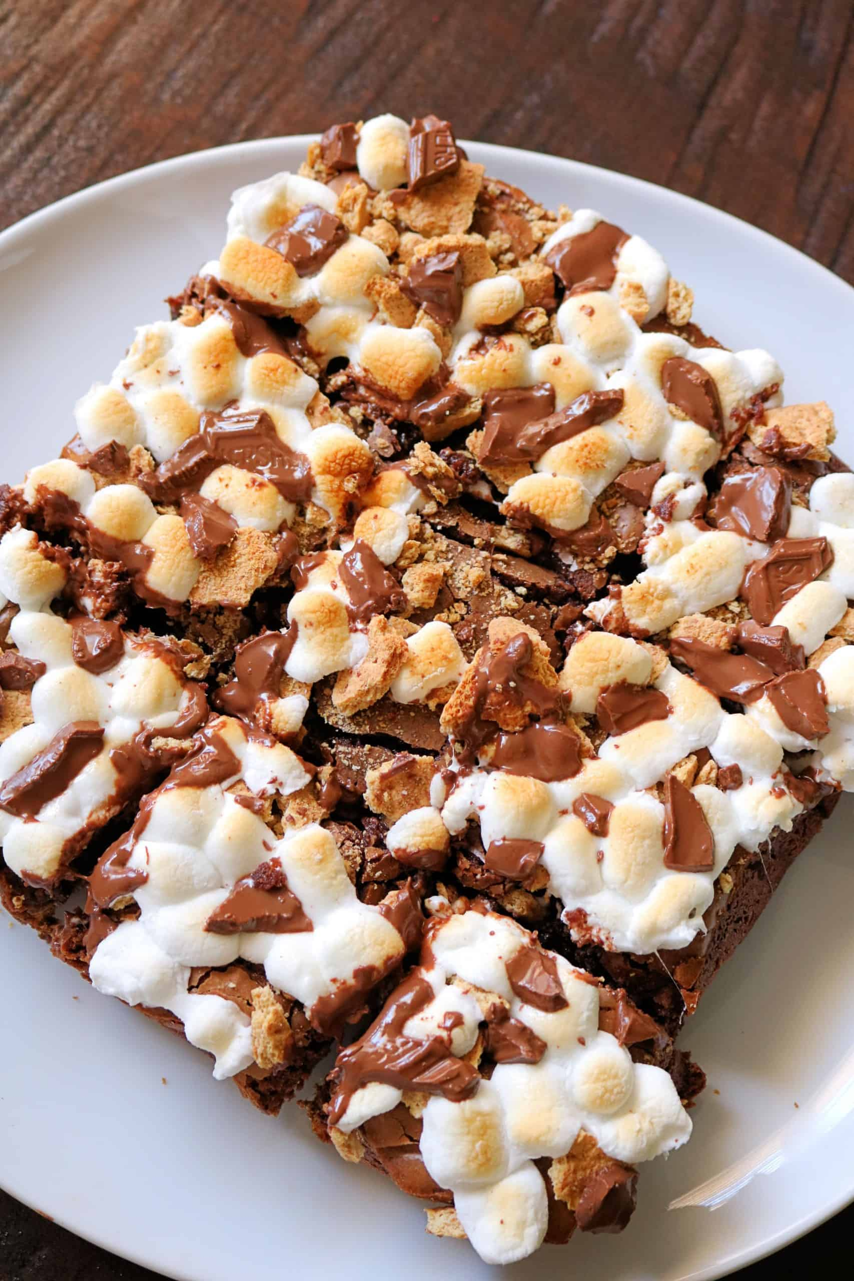 These Easy Fudge S'mores Brownies made from a box mix are incredibly delicious and decadent! A graham cracker crust is covered with a layer of rich, fudgy brownies with chocolate chips and topped with toasted miniature marshmallows, chopped up Hershey's bars, and crushed graham cracker pieces. The perfect summertime s'mores dessert! #brownies #smores  #dessert #easybrownies