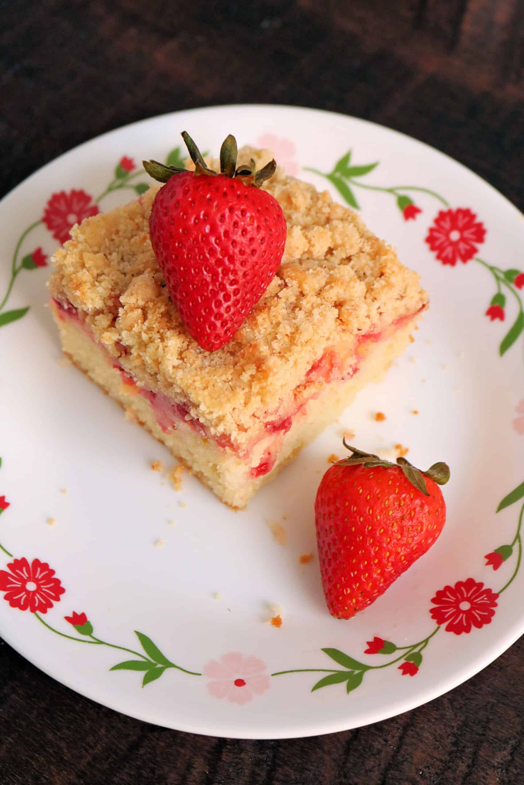 This Fresh Strawberry Coffee Cake with Crumb Topping is so delicious and easy to make! Homemade, soft vanilla butter cake with sour cream, fresh strawberries, and a brown sugar cinnamon crumb topping make one perfect breakfast treat or dessert! #strawberrycake #coffeecake #breakfast #dessert #easyrecipe