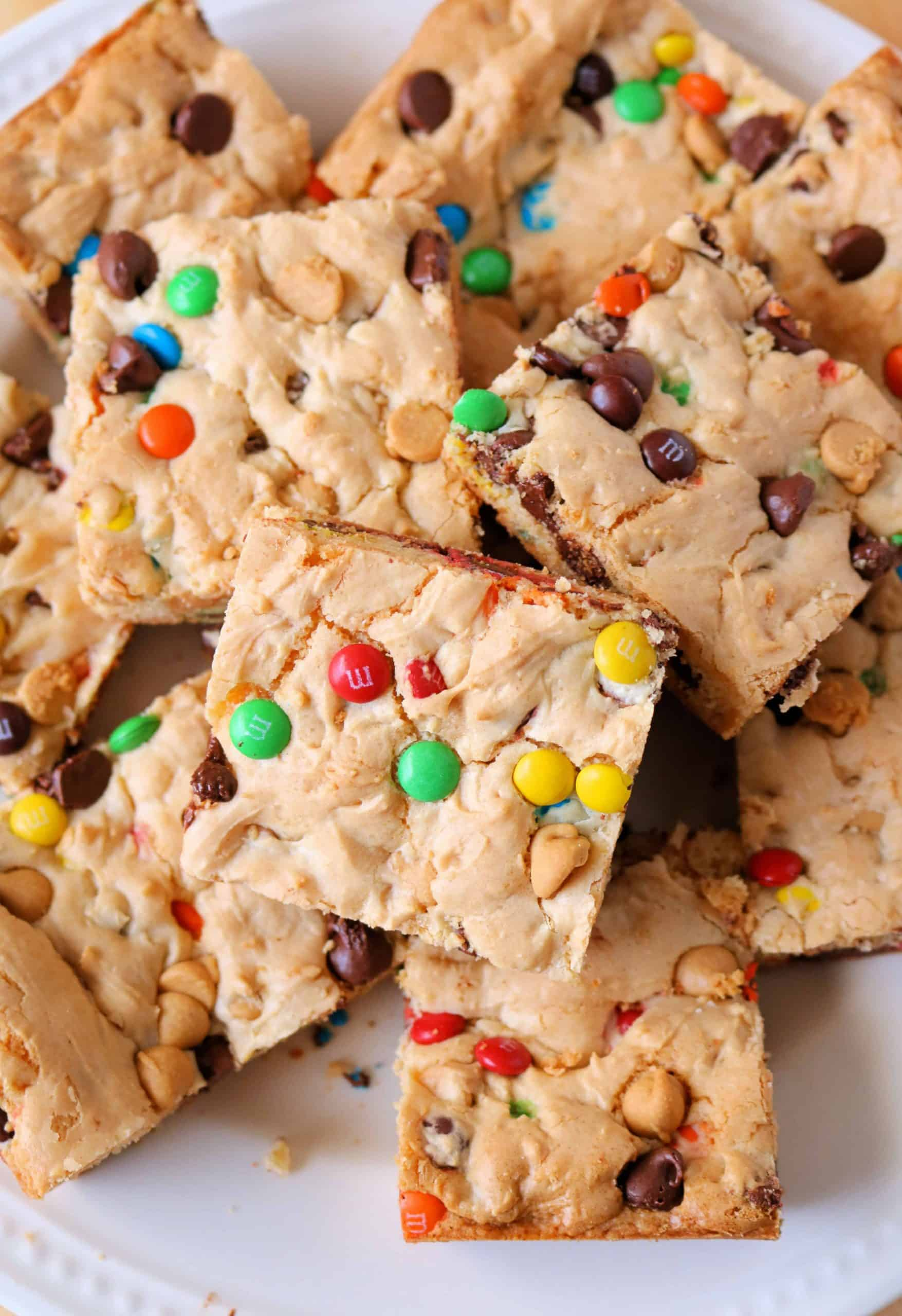 Try my Delicious Loaded Cake Mix Cookie Bars for an easy dessert! These cake mix bars are made in less than 25 minutes with just a few ingredients including a boxed white or yellow cake mix, chocolate chips, peanut butter chips, and mini M&M's. #cakemixbars #cookiebars #dessertbars #lazybars