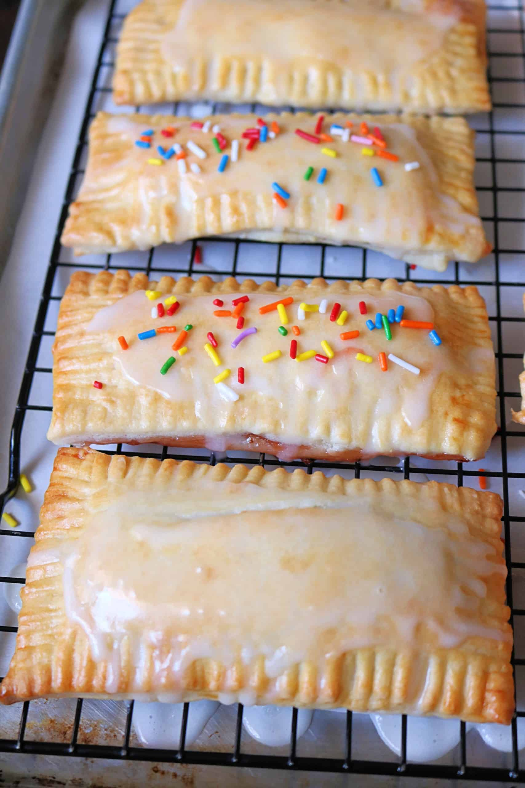 Learn how to make these easy and delicious homemade pop tarts in 3 flavors including Strawberry, Blueberry, and Brown Sugar Cinnamon. These pop tarts are made from scratch with an easy pie crust dough, filled with a delicious filling, and topped with a vanilla sugar icing and sprinkles. #poptarts #pastry #breakfast #dessert