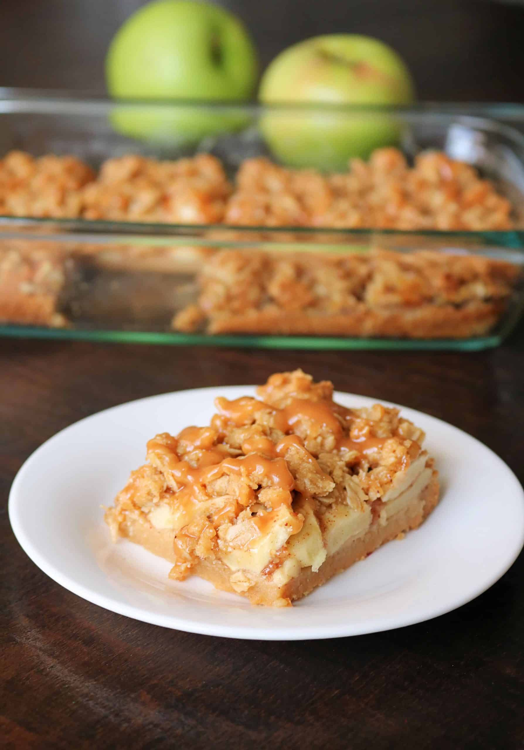 Try these Easy Salted Caramel Apple Pie Bars for a delicious fall or Thanksgiving dessert!  These caramel apple pie bars have a buttery shortbread crust and are made with granny smith apples, a brown sugar-cinnamon oat streusel topping, and are drizzled with an easy homemade salted caramel sauce. The most delicious apple pie bar you'll ever eat! #applepiebars #applepie #saltedcaramel #caramelapple #falldessert