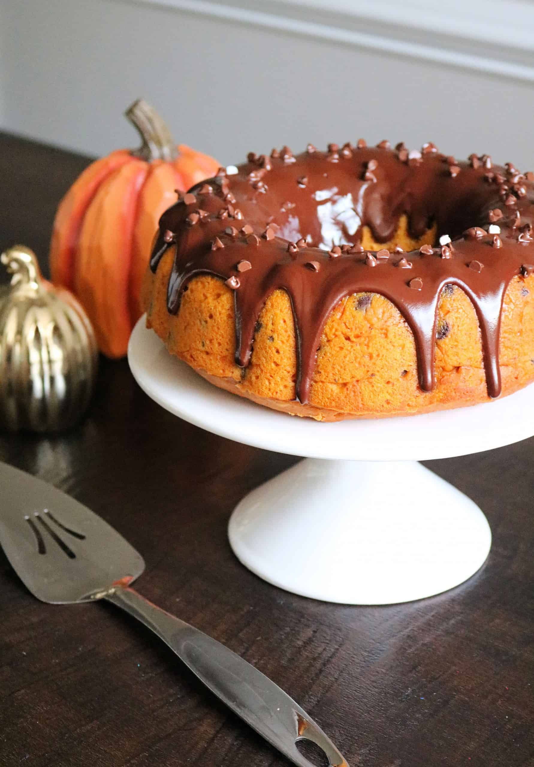 Make this Delicious and Easy Pumpkin Chocolate Chip Bundt Cake for Fall or Thanksgiving! The homemade pumpkin cake is moist and flavorful with pumpkin spices, loaded with chocolate chips, and topped with a beautiful chocolate ganache glaze. #pumpkincake #cake #falldessert #pumpkinrecipe