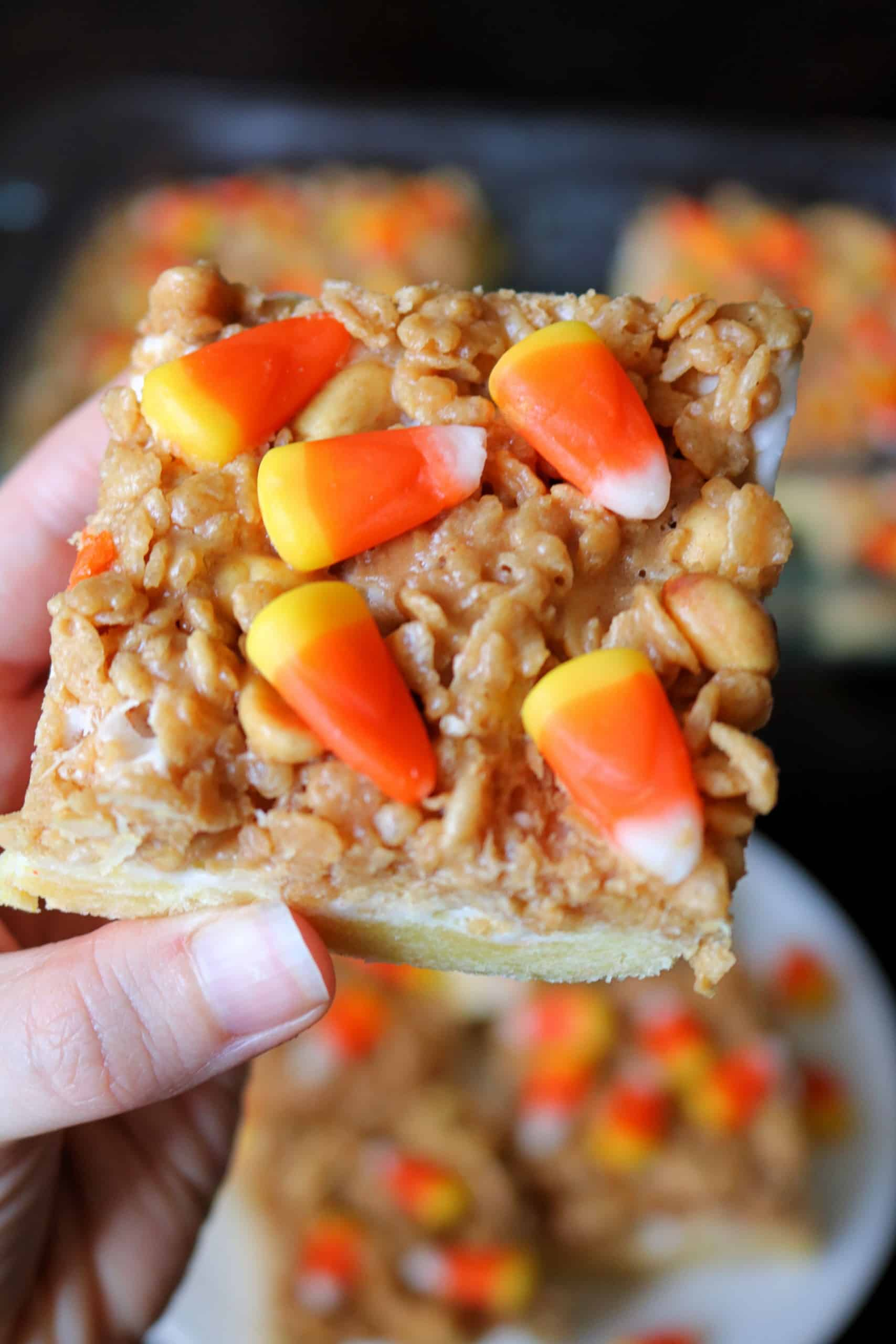 Love candy corn? Try my delicious and easy Sweet and Salty Candy Corn Bars for the perfect fall  or Halloween dessert! These candy corn bars feature a cake bar crust, and are topped with peanuts, marshmallows, rice krispies, peanut butter, and candy corn . #candycorn #candycornbars
