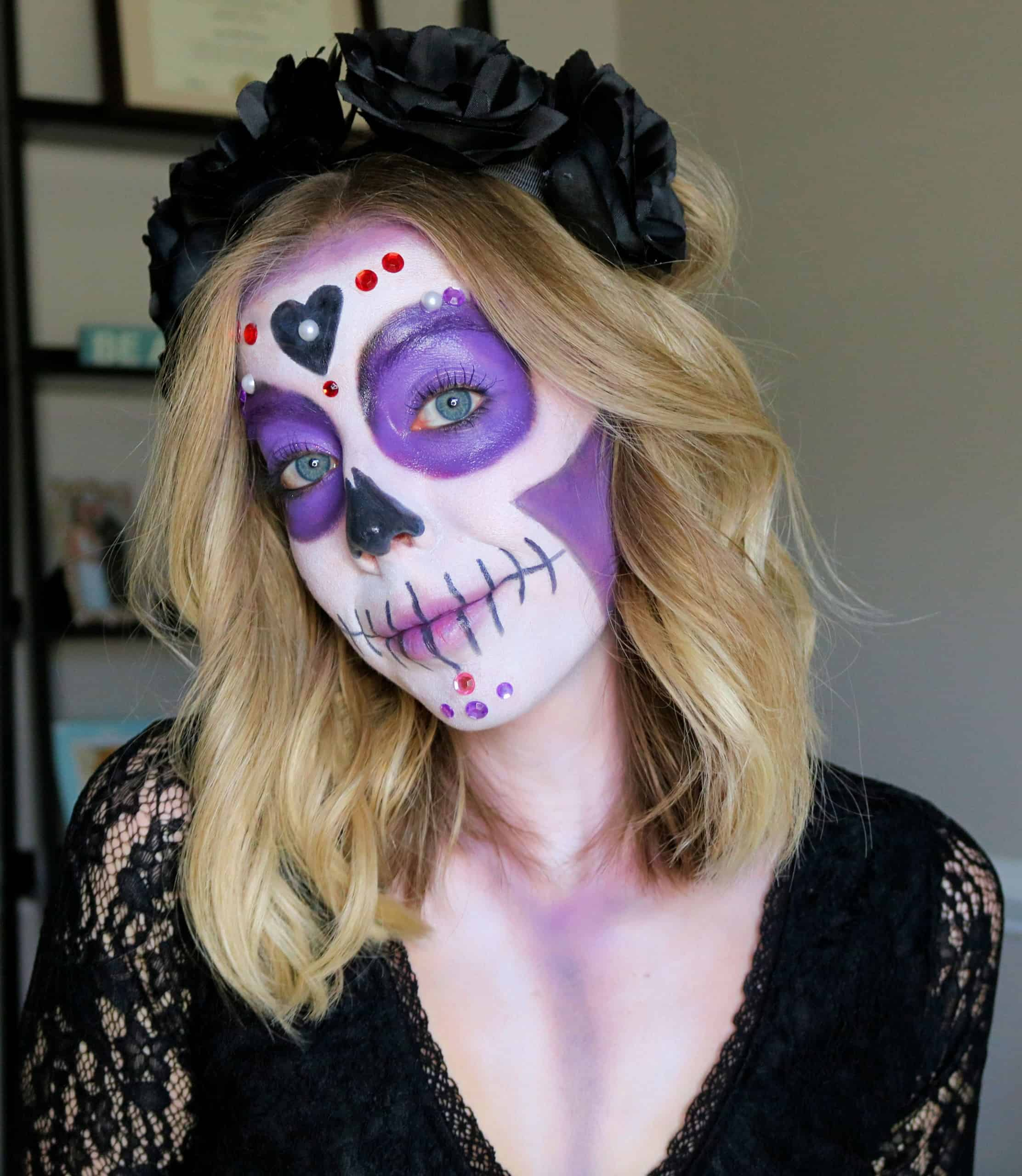 Learn how to create a beautiful, purple sugar skull makeup for Halloween or Day of the Dead using my Easy Sugar Skull Makeup Tutorial! This simple, pretty, and colorful sugar skull is perfect for beginners and uses affordable drugstore makeup products, glitter, and rhinestone jewels. #sugarskullmakeup #sugarskull #halloweenmakeup #dayofthedead