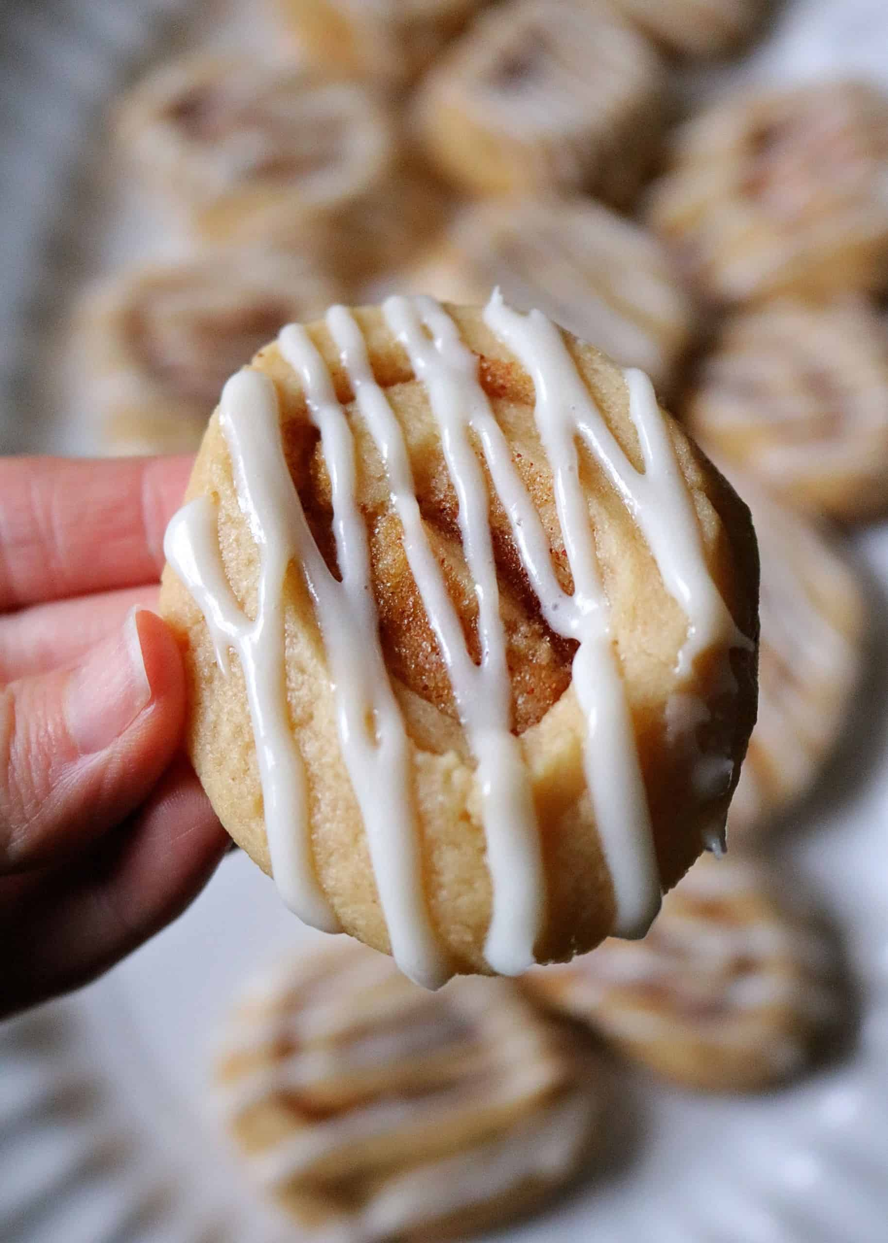 Love soft, gooey Cinnamon Rolls? Then try my delicious and easy homemade cinnamon roll cookies! They feature a soft, buttery sugar cookie with swirls of cinnamon sugar, and cream cheese icing glaze drizzled on top. #cookies #cinnamonrollcookies #christmascookies #baking