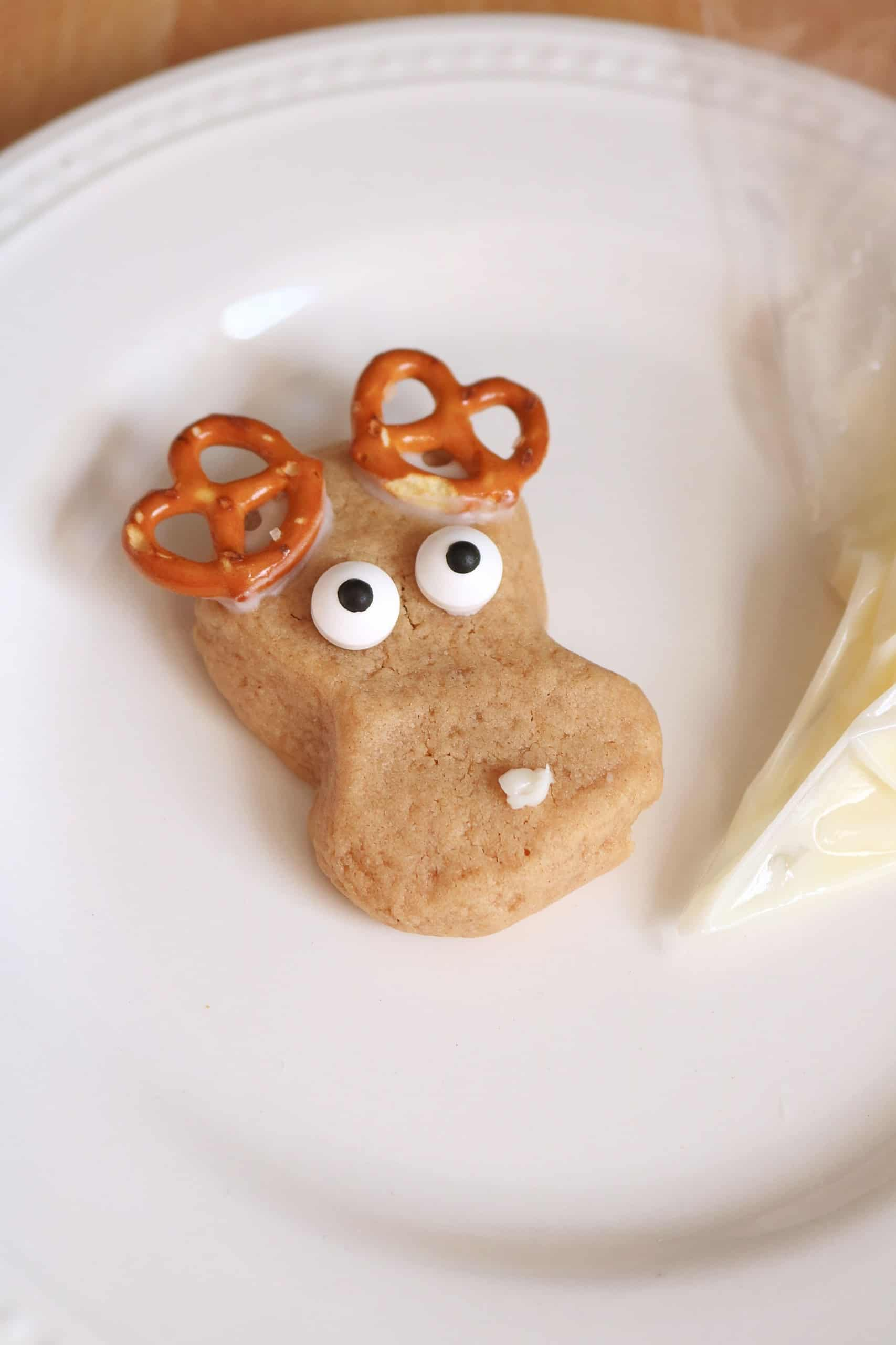 These Easy Peanut Butter Reindeer Cookies are made with my delicious homemade peanut butter cookie dough and decorated with pretzels, candy eyes, melted white chocolate, and M&Ms. Kids and adults will love these yummy, cute, and fun reindeer Christmas cookies! #christmascookies #cookies #reindeercookies #peanutbuttercookies