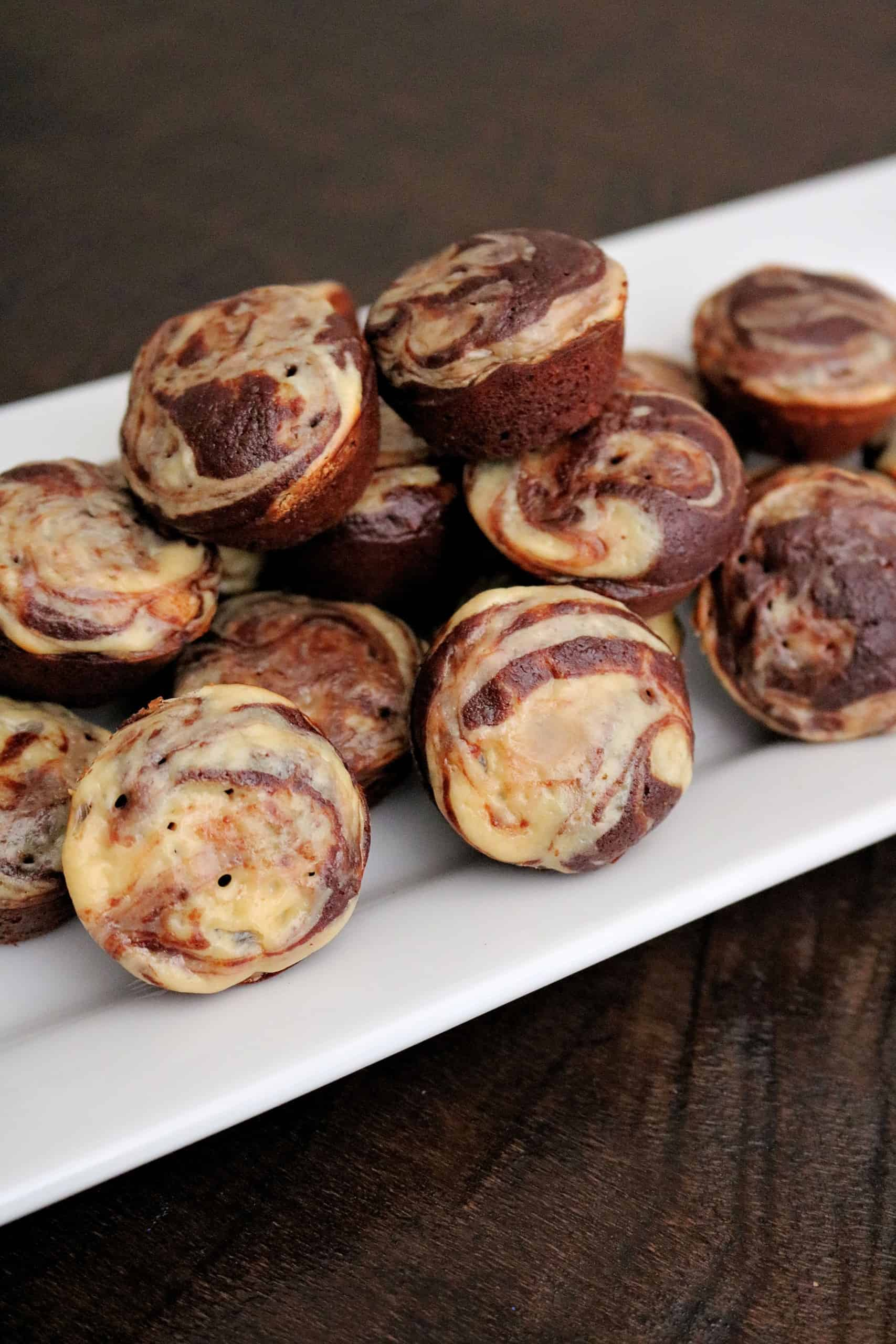 These Skinny Cheesecake Swirl Brownie Muffins are so delicious and easy to make in just 25 minutes! These fudgy, bite-sized brownie muffins are swirled with delicious, light cream cheese and will become your new favorite afternoon snack or healthy dessert! #browniemuffins #browniebites #cheesecakebrownies #healthybrownies